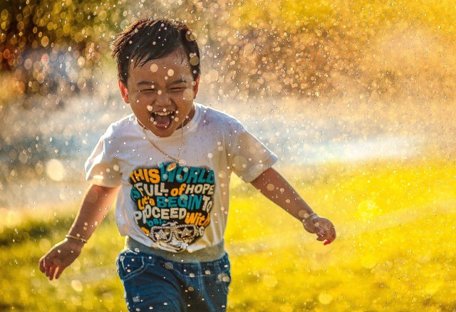 Boy running in water spray